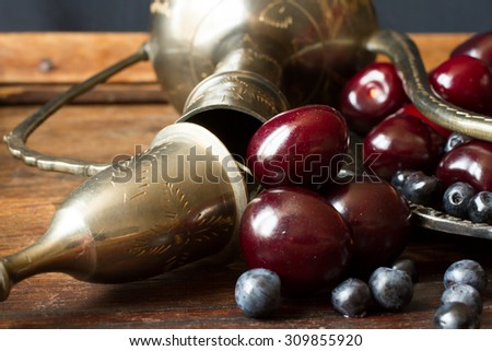 cherry with red currants and blueberries in a jug and a metal plate in oriental style on a background of wood.