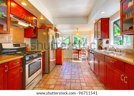Cherry wood kitchen with tile floor and sunny table home interior. - stock photo