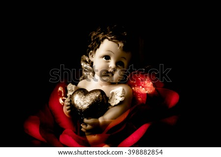 Cherub angel statue with heart,Double exposure cherub angel with rose,Love concept - stock photo