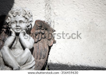 cherub statue against a wall with copy space