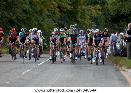 CHESHAM, UK - SEPTEMBER 12: The chasing peloton heads toward the finish line in Hemel Hempstead after cycling from Bath as part of the Tour of Britain cycling race on September 12, 2014 in Chesham  - stock photo