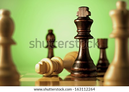 Chess, a game of skill and planning with the winning dark king chess piece declaring check mate on the fallen light wood king in a concept of winning and leadership - stock photo