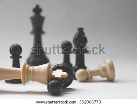 chess battle - fallen king - plastic chess pieces - stock photo