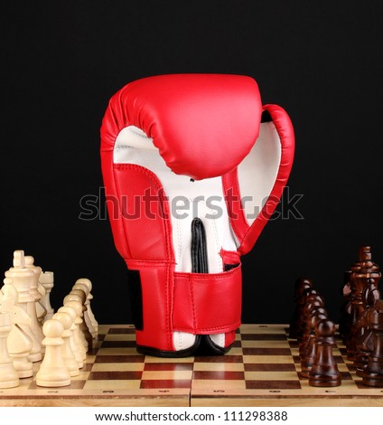Chess board and boxing glove isolated on black - stock photo