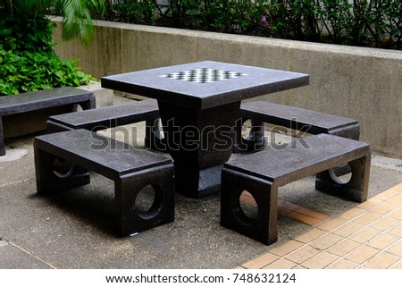Chess Board On Top Of Stone Table And Bench In The Park.