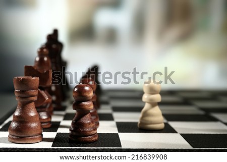 Chess board with chess pieces on dark background - stock photo