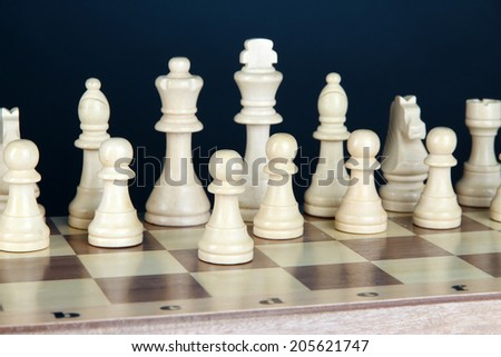 Chess board with chess pieces on dark color background