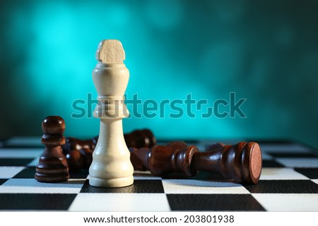 Chess board with chess pieces on light blue background - stock photo