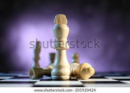Chess board with chess pieces on purple background - stock photo