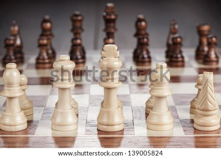 chess board with figures on the brown wooden table background - stock photo