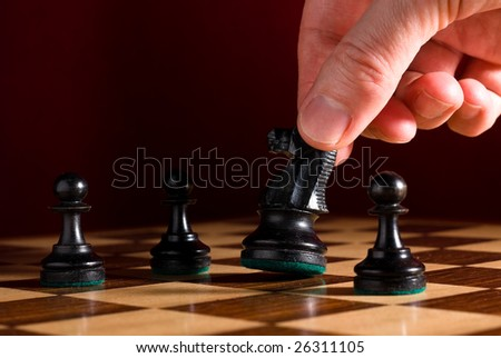Chess board with pieces as example of game or business concept for power; strategy or success with hand moving knight - stock photo