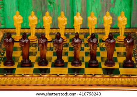 Chess board. wooden figures . carved wooden chess . yellow and brown. high relief and chess. beautiful pieces of handmade chess  - stock photo