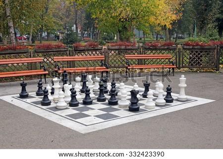chess figures in park autumn season - stock photo