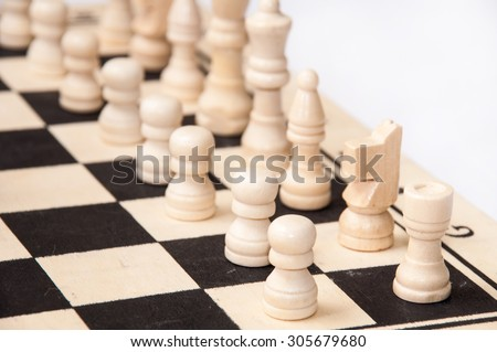 Chess figures lined up on a chess board. - stock photo