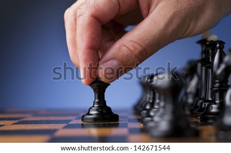 chess game, chess player makes a move the black pawn forward - stock photo
