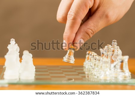 Chess glass start up game with your hand. - stock photo