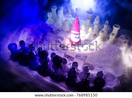 Chess in the snow. winter concept. Christmas or New Year present on a chessboard with Santa Claus on a dark background. Copy space. Selective focus