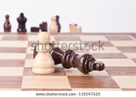 Chess king lying near the pawn