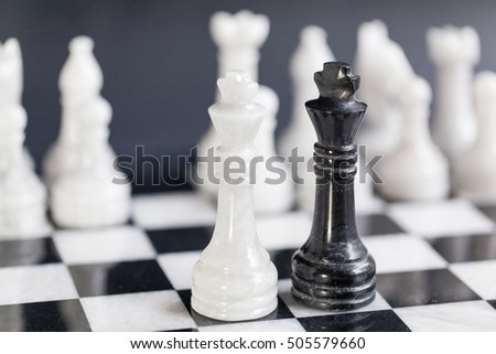 Chess Kings facing each other as a business concept - merger & partnership, or showdown, corporate takeover, strategy, competition, opposition, confrontation, politics, leadership, challenge, survival