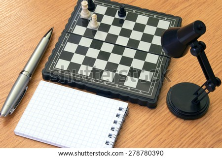 Chess lamp notebook and pen on the table - stock photo