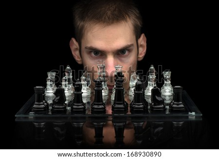 Chess Master staring at you with intense eyes behind glass chess pieces on a glass chessboard with a reflection isolated on a black background