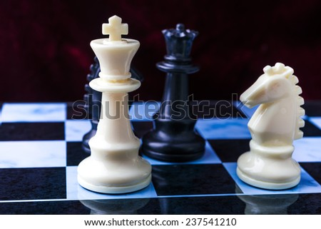 Chess on the chessboard. Black and white chess pieces on blue board - stock photo