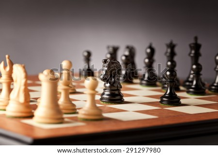 Chess opening - initial phase of a chess game - black knight and pawns facing the white pieces