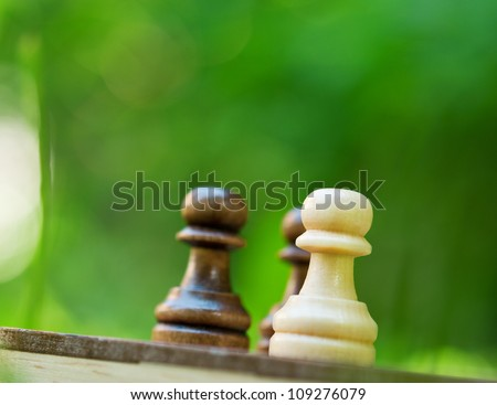 chess pawns on the board on green background