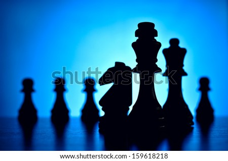Chess pices silhouetted against a blue background with a king flanked by a knight and queen in the foreground facing off against a row of pawns depciting strategy, skill and planning - stock photo