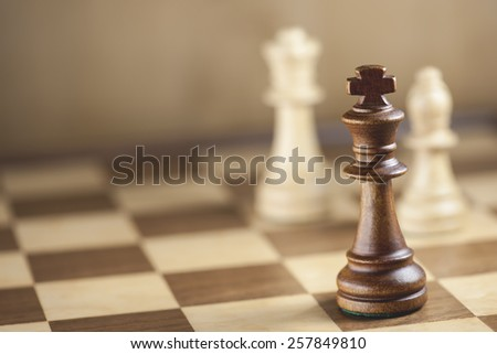 Chess pieces and game board background - stock photo