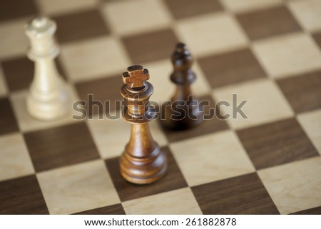 Chess pieces and game board background; focus on king (Shallow DOF) - stock photo