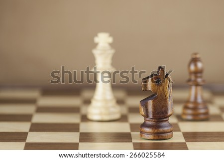 Chess pieces and game board background; focus on knight (Shallow DOF) - stock photo