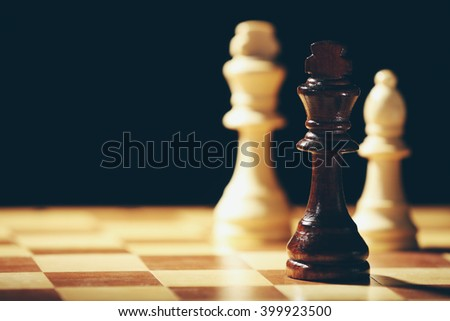 Chess pieces and game board on black background - stock photo