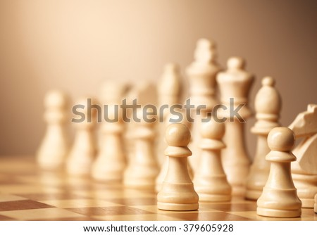 Chess pieces and game board on brown background - stock photo