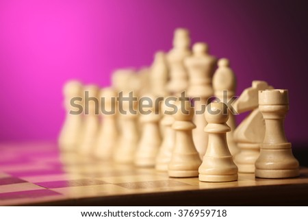 Chess pieces and game board on purple blurred background