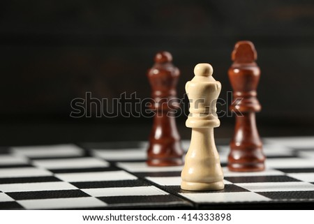 Chess pieces and game board on wooden background - stock photo