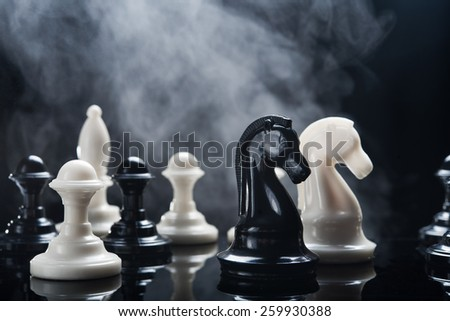 Chess pieces and smoke at background - stock photo