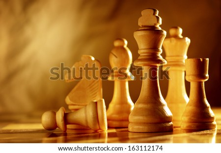 Chess pieces in light wood grouped together on a chessboard, low angle view with sepia toned lighting and copyspace - stock photo