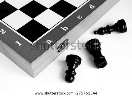 Chess pieces on a chessboard on a light background. Black - white image. - stock photo