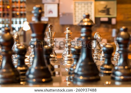 chess pieces on a table in a living room - stock photo