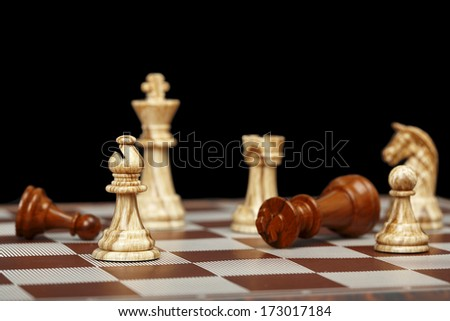 chess pieces on chessboard against black - stock photo