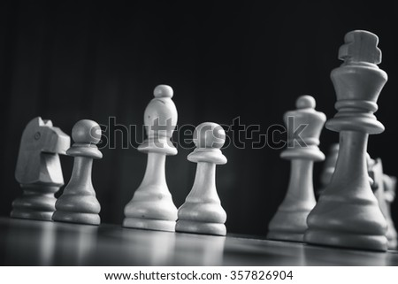 Chess pieces on the board. Black wood background behind. - stock photo