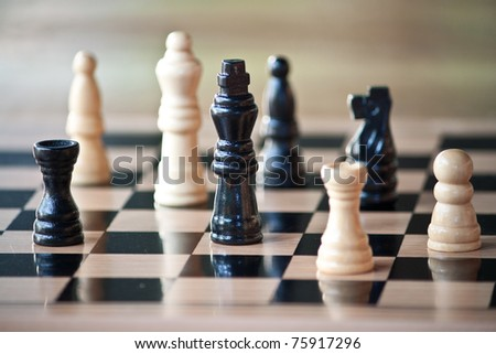 Chess pieces on wood board - stock photo