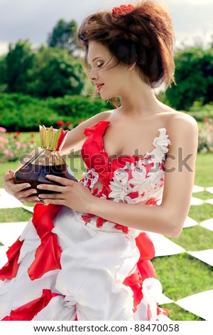 Chess queen holds a large bottle of perfume - stock photo