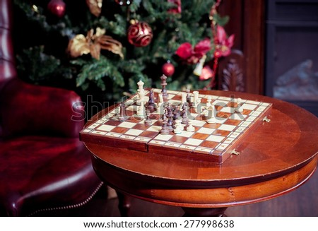 Chess set on a table with leather chair background - stock photo