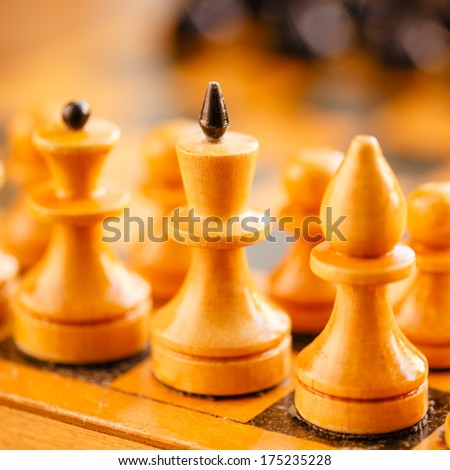 Chess standing on ancient wooden chessboard - stock photo