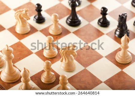 Chess tactics - wooden chess pieces on a chessboard - stock photo