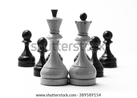 Chess white king and queen before a few black pawns on a white background