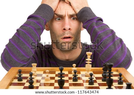 Chessboard with desperate man thinking about chess strategy, isolated on white - stock photo