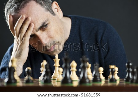 Chessboard with man thinking about chess strategy - stock photo